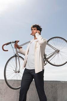 自転車の横でポーズをとる若い男