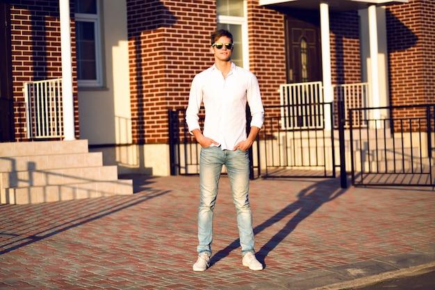 Молодой человек позирует на улице, элегантный повседневный образ, теплые солнечные тона, молодой бизнесмен, идущий один, модные солнцезащитные очки, белая рубашка.
