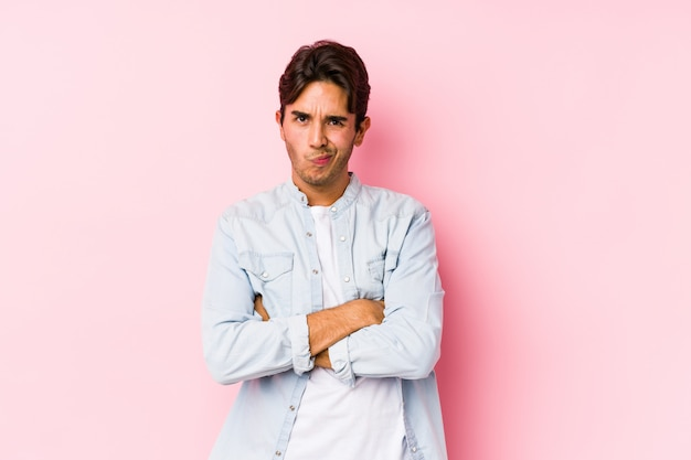 Young man posing in a pink wall isolated frowning face in displeasure, keeps arms folded