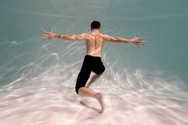 Young man posing submerged underwater