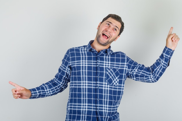 Young man posing while pointing fingers away in checked shirt and looking energetic