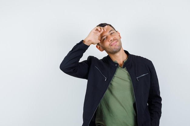 Молодой человек позирует, стоя в футболке, куртке и выглядит веселым. передний план.