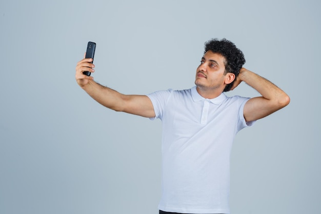 Молодой человек позирует во время селфи в белой футболке и выглядит мило. передний план.