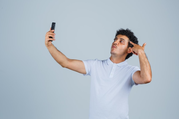 Young man posing while taking selfie on mobile phone in white t-shirt and looking confident , front view.
