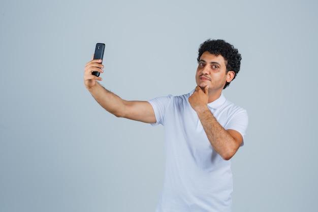 Giovane che posa mentre prende selfie in maglietta bianca e sembra carino. vista frontale.