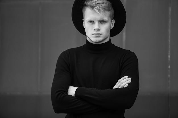 도시 배경에 검은 옷과 함께 포즈 젊은 남자.