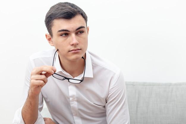 Молодой человек позирует в очках в руке