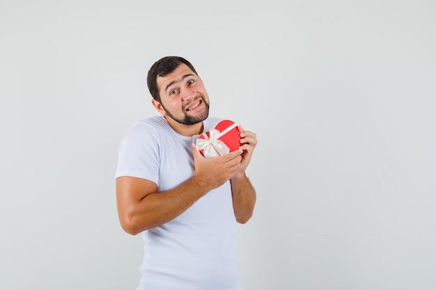 Молодой человек позирует с коробкой в форме сердца в белой футболке и выглядит весело. передний план. место для текста