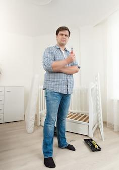 침실에서 분해 된 아기 침대에서 도구로 포즈를 취하는 젊은 남자