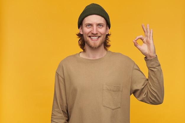 Молодой человек, позитивный улыбающийся парень со светлыми волосами, бородой и усами. в зеленой шапке и бежевом свитере. показываю знак