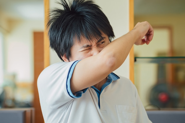 Young man in posture of elbow cough which is correct sneezing