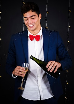 Young man pouring champagne in glass