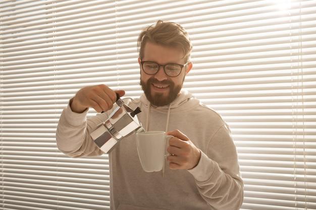 朝、モカポットからコーヒーを注ぐ若い男。朝食と休憩のコンセプト。