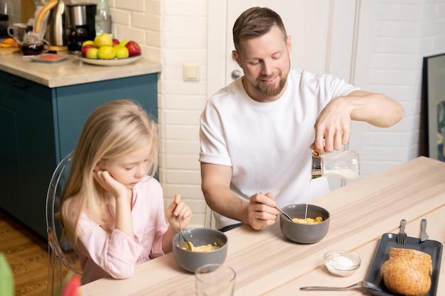 Молодой человек наливает свежее молоко в серую фарфоровую миску с мюсли или кукурузными хлопьями, завтракая со своей милой маленькой дочкой