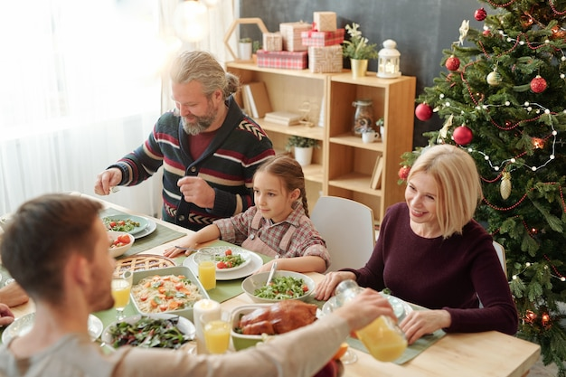 Young man pouring orange juice for his happy mom sitting against decorated christmas tree during family dinner at home