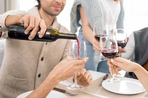 Молодой человек наливает красное вино из бутылки в бокалы своих друзей во время празднования праздника за столом вместе
