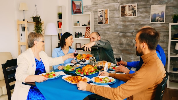 家族の夕食で彼の母親に赤ワインを注ぐ若い男。