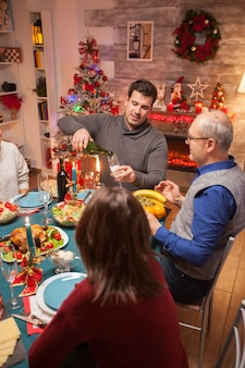 Young man pouring wine to his father at christmas family dinner. christmas celebration with delicious food.
