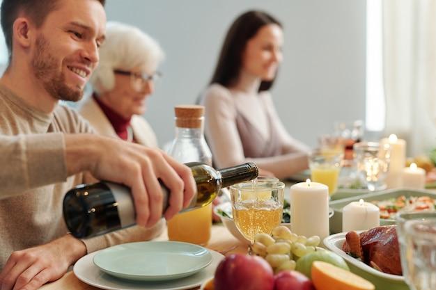 Молодой человек наливает вино в бокал, сидя за обслуживаемым столом во время семейного ужина в день благодарения