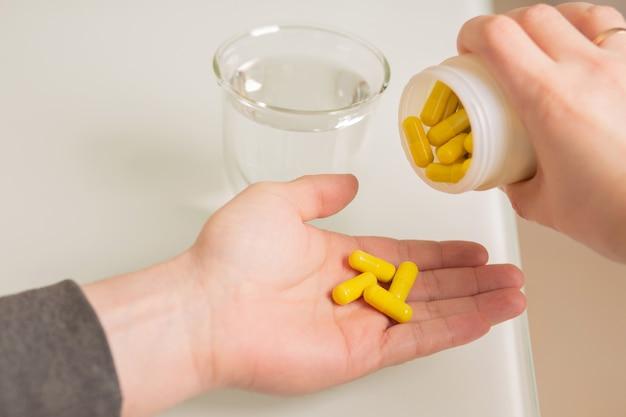젊은 남자는 병에서 알약 캡슐을 부습니다. 백그라운드에서 물 유리
