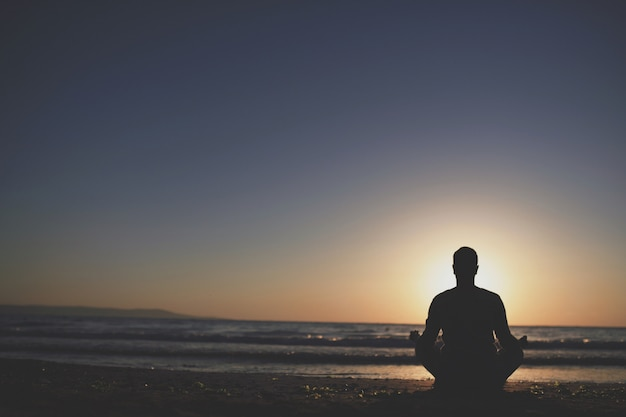 Young man practice yoga on the beach at sunset.