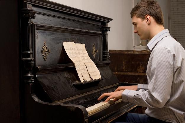 ピアノで練習する若い男