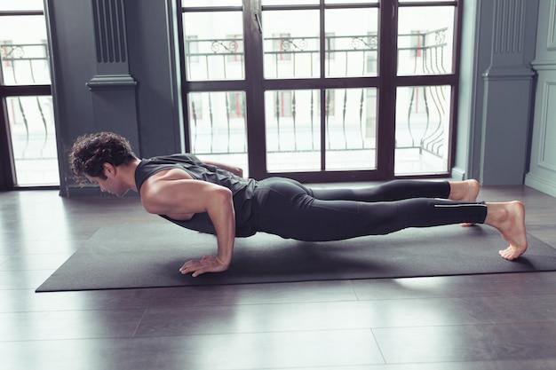 Young man practicing basic yoga pose chaturanga dandasana