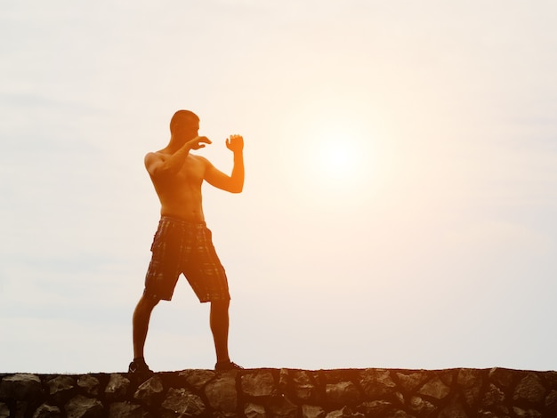 Young man practicing boxing outdoors