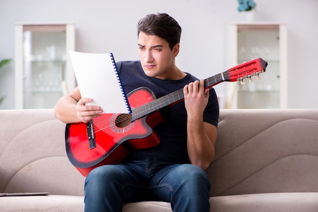 Young man practicing playing guitar at home
