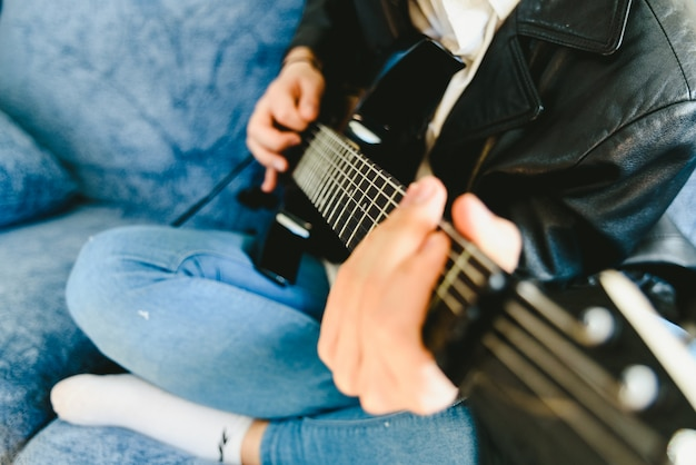 Young man practicing with his electric guitar on the sofa of his house learning.