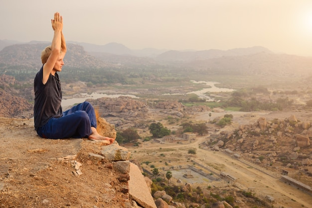 ハンピ、インドの日の出の山の崖でヨガを練習している若い男