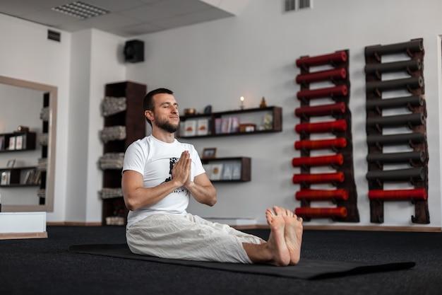 체육관에서 요가를 연습하는 젊은 남자.