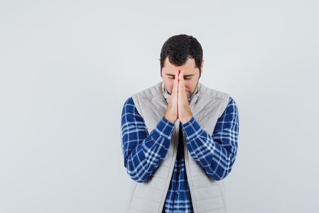 シャツ、ノースリーブのジャケットで何かを祈って、焦点を当てた、正面図を探している若い男。