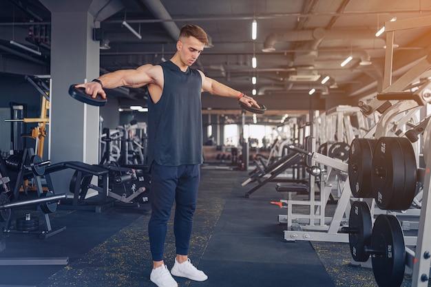 덤벨 레터 럴 레이즈를 준비하는 젊은 남자-어깨 운동