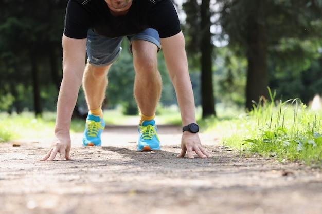젊은 남자는 공원 개념에서 낮은 출발부터 달릴 준비를 합니다.