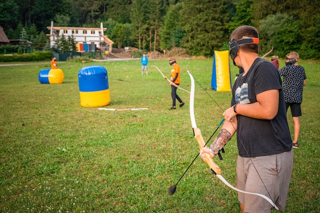Young man preparing for an attack while playing archery tag