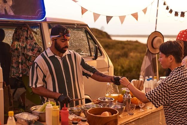 Молодой человек готовит фаст-фуд и лечит молодых людей на пляжной вечеринке на открытом воздухе