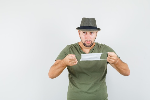 Young man preparing to wear medical mask in green t-shirt and hat and looking puzzled