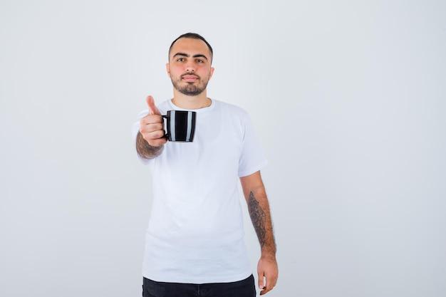 白いtシャツと黒のズボンでお茶を提示し、幸せそうに見える若い男