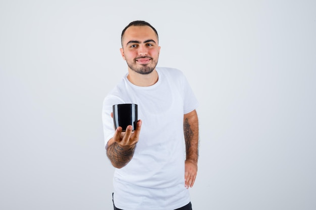 Young man presenting cup of tea while holding hand on waist in white t-shirt and black pants and looking happy