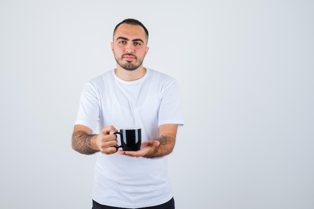 Young man presenting cup of tea in white t-shirt and black pants and looking serious
