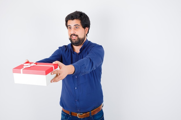 Young man presenting gift box in blue shirt and jeans and looking serious , front view.