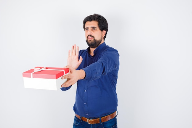 Young man presenting gift box and showing stop sign in blue shirt and jeans and looking scared , front view.