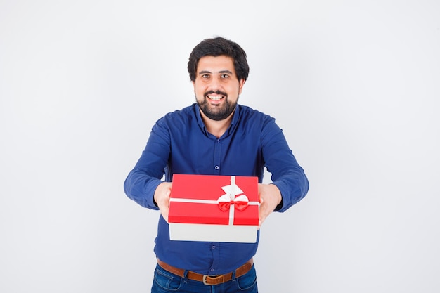 Young man presenting gift box with both hands in blue shirt and jeans and looking optimistic. front view.