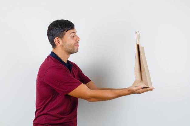 티셔츠에 종이 가방을 제시하고 기뻐 보이는 젊은 남자, 전면 보기.