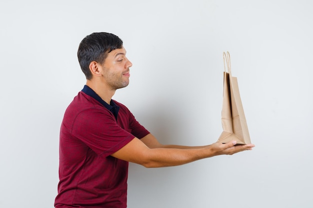 Young man presenting paper bag in t-shirt and looking glad , front view.