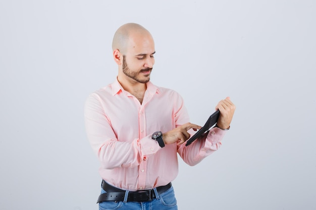 ピンクのシャツ、ジーンズの正面図で電卓のボタンを押す若い男。
