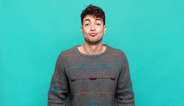 Молодой человек сжимает губы вместе с милым, веселым, счастливым, прекрасным выражением лица, отправляя поцелуй