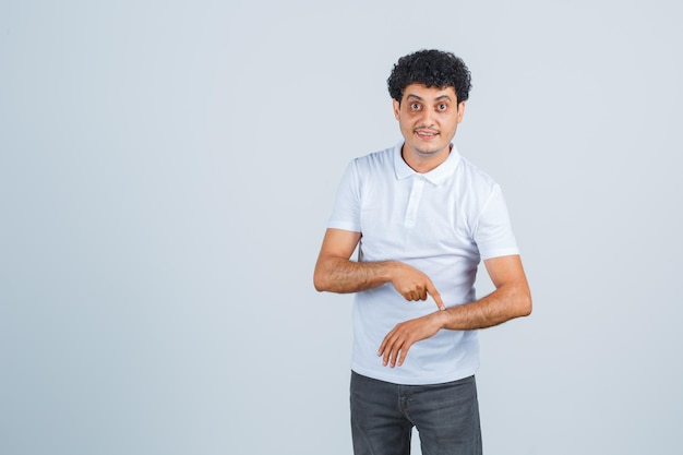 Young man pretending like pointing index finger to clock in white t-shirt and jeans and looking optimistic , front view.