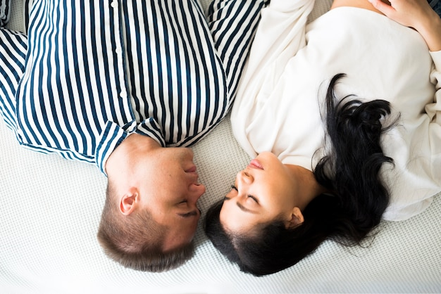 Young man and pretty ethnic woman sleeping on bed face to face